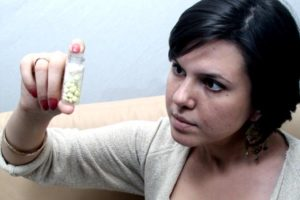 девушка смотрит на пузырек с таблетками