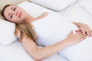 женщина страдает от боли в животе