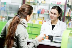 девушка покупает лекарства в аптеке