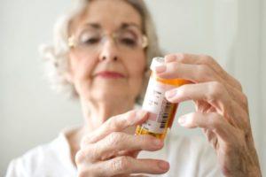 пожилая дама изучает таблетки