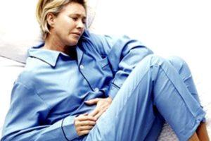 женщина в пижаме лежит, схватившись за живот
