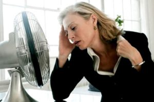 женщина сидит у вентилятора