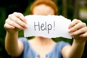 женщина держит записку с просьбой помочь