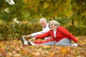пожилая пара делает растяжку