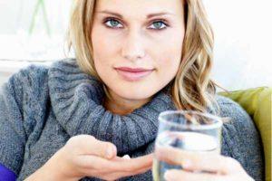 женщина пьет тааблетки