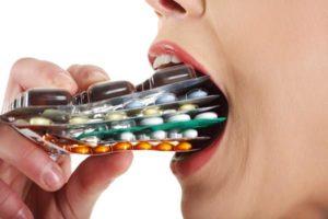 женщина запихивает в рот стопку лекарств