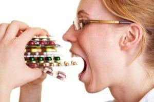 девушка запихивает в рот пачку таблеток
