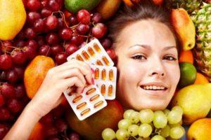 женщина лежит во фруктах и держит витамины
