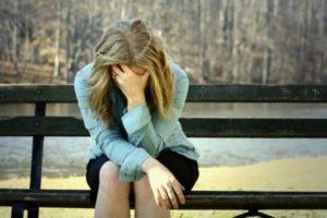 девушка сидит на скамейке и держится за голову