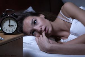 девушка не спит и смотрит на будильник