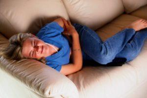 женщина лежит на диване с болью в животе