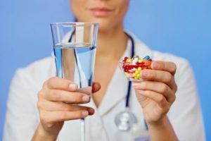 в руках у медсестры вода и таблетки