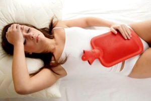 девушка лежит на кровати с грелкой на животе