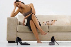 уставшая девушка сидит на диване