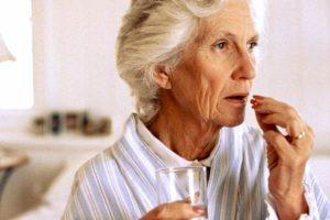 пожилая дама пьет таблетки