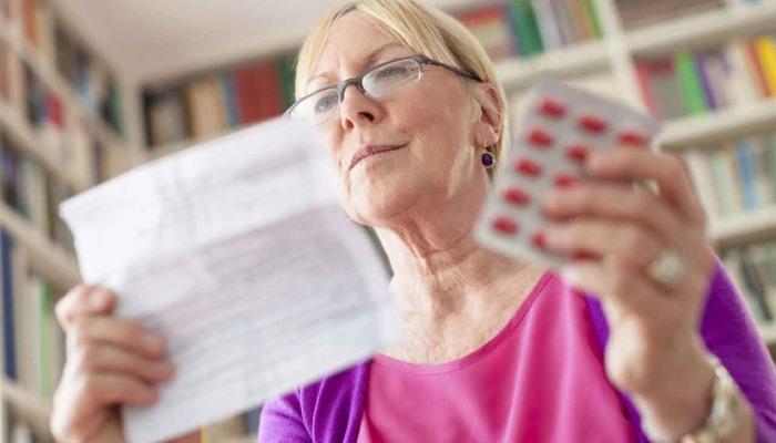 женщина читает инструкцию к таблеткам