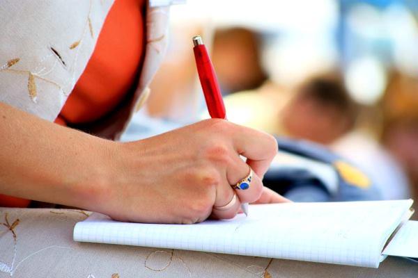 в руке ручка пишет на бумаге